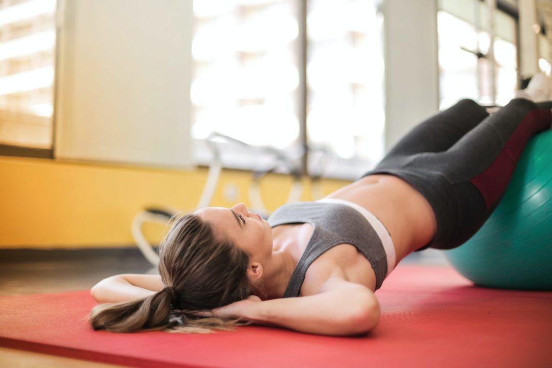 Femme sur un tapis de sol et swiss-ball
